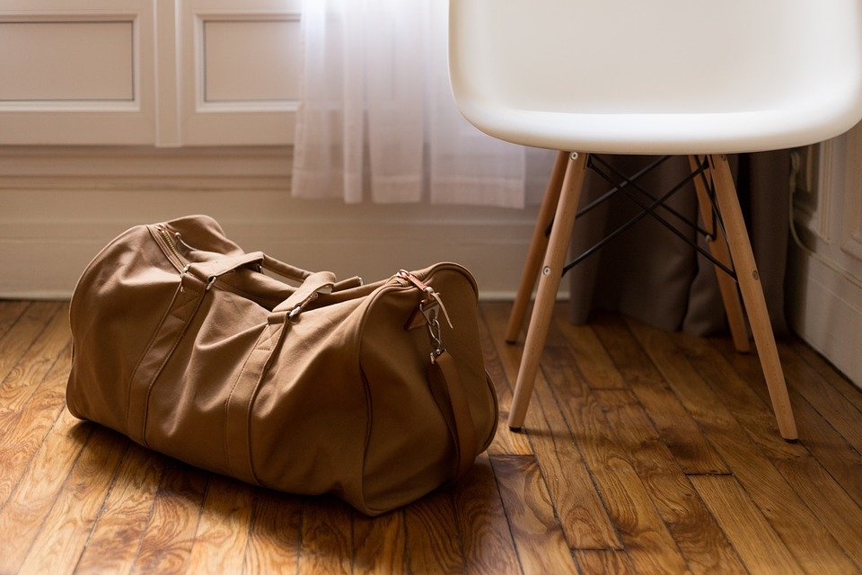 packed brown bag sitting next to a white chair on the wooden floor.